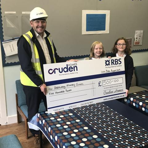 Andy Brown, Contracts Manager for Meadowside, Aberlady, presenting the cheque to two pupils at Aberlady Primary school